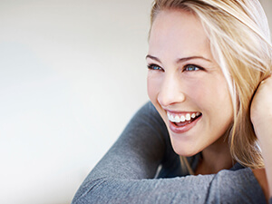 lady in gray sweater with big smile
